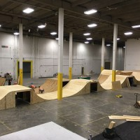 Workers build ramps inside the B-Line Indoor Bike Park BMX centre, which will open in August in Calgary. It's part of a trend toward more indoor sports and recreation facilities.